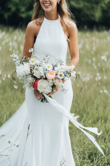Bride in Halterneck Made With Love Wedding Dress Holding a White Peony and Pastel Flower Bouquet in a Field