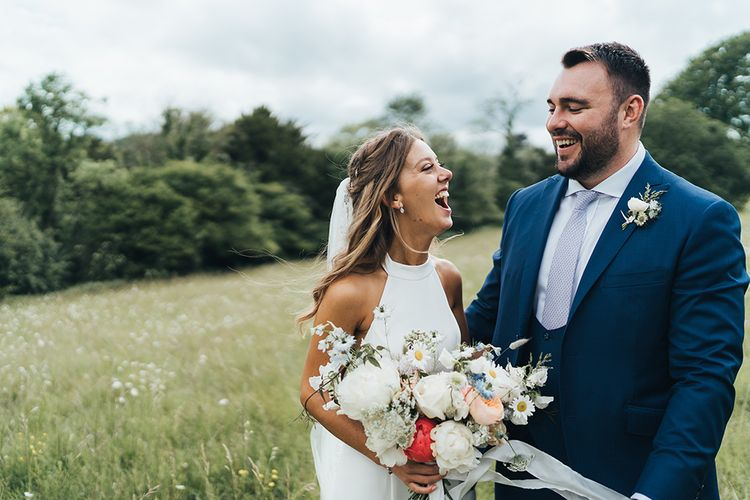Bride in Halterneck Wedding Dress Holding a Pastel Wedding Bouquet Laughing with Her Groom in a Field