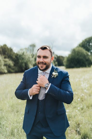 Groom in Three Piece Navy Suit with Horseshoe Waistcoat Adjusting His Tie in a Field