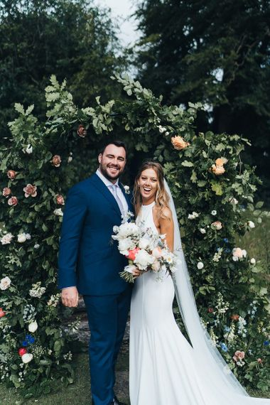 Bride in Fitted Wedding Dress Holding a Pastel Bouquet and Groom in Navy Suit Standing in Front of a Flower Arch