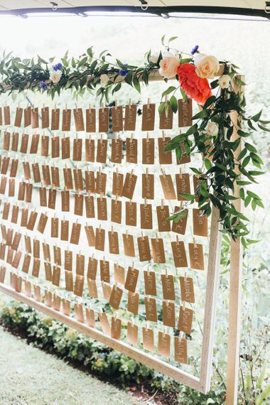 Craft Paper Escort Cards Pegged on a Giant Wooden Frame Decorated with Vine and Flowers