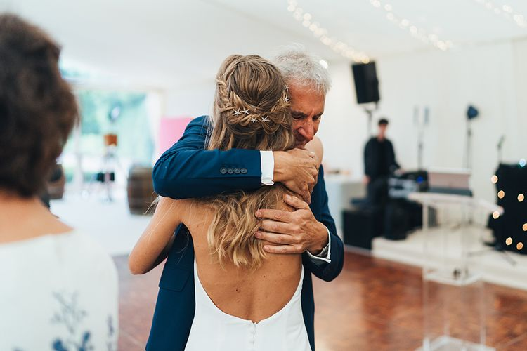 Father of the Bride cuddling His Daughter with Half up Half Down Braided Hair Accessorised with Tilly Thomas Lux Hair Slides