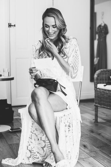 Bride Wears Lace Getting Ready Robe During Preparations For Barn Wedding
