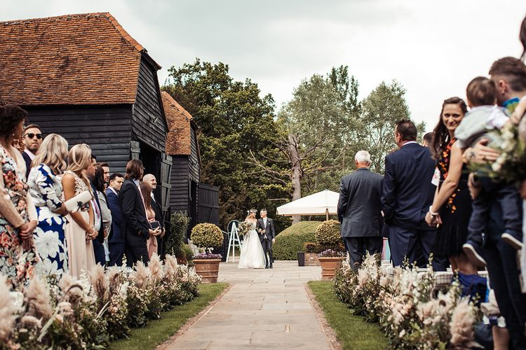 Barn Wedding With Bride Walking Down The Aisle