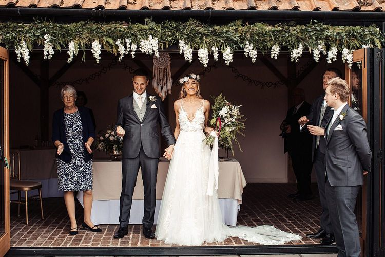 Bride and Groom During Outdoor Ceremony With Flower Decor and Dream Catchers