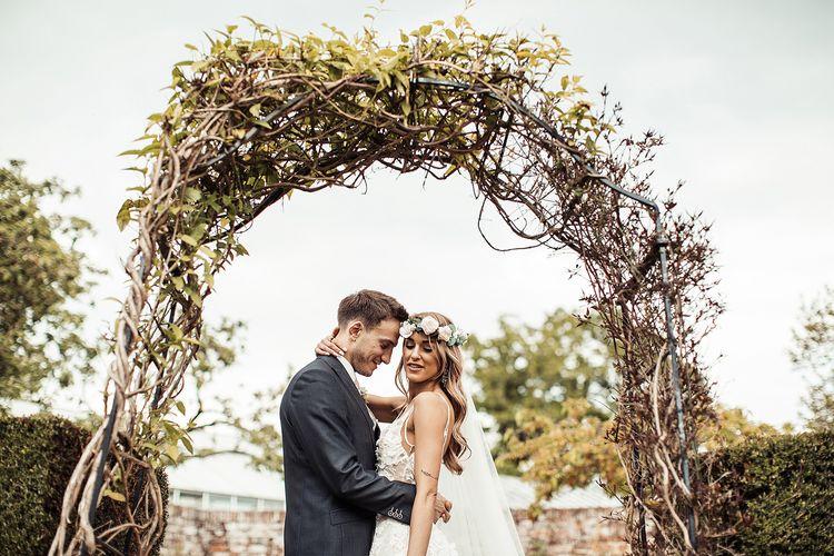 Bride and Groom at Barn Wedding Under Flower Arch