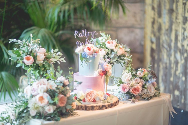 Pretty wedding cake in pink and green with flower decor