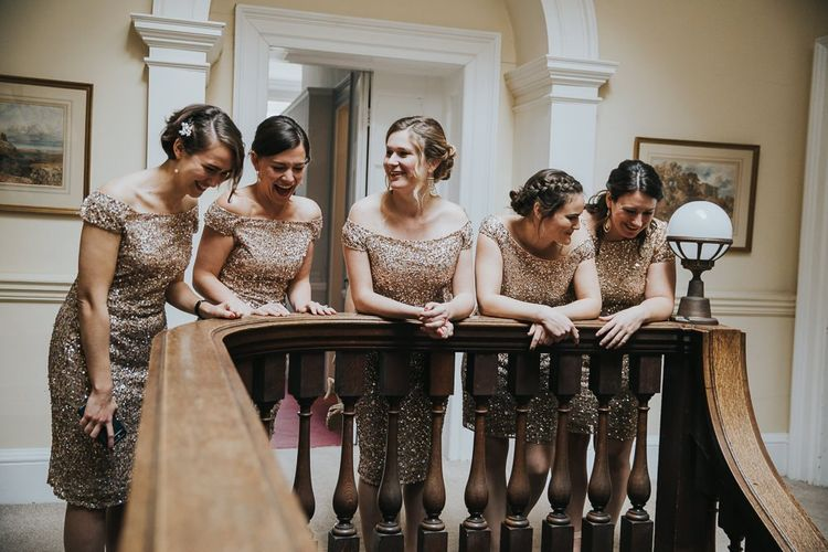 Bridesmaids in Gold Dresses Peer Over Staircase