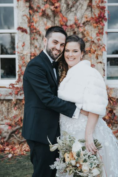 Groom Wears Tux and Bride Wears Faux Fur Cover Up For Winter Wedding at Kirtlington Park Wedding Venue