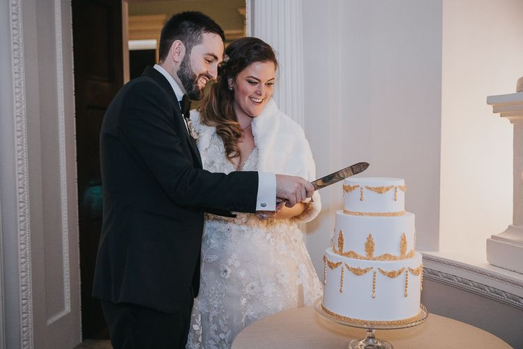 Bride and Groom Cut The Cake with Gold Detail