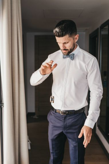 Groom in Navy Trousers, White Skirt and Floral Bow Tie