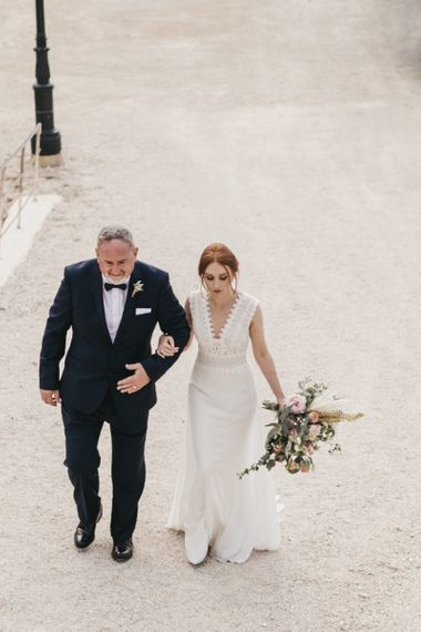 Father of the Bride in a Tuxedo and Bride in a Fitted Pronovias Wedding Dress Walking to the Wedding Ceremony