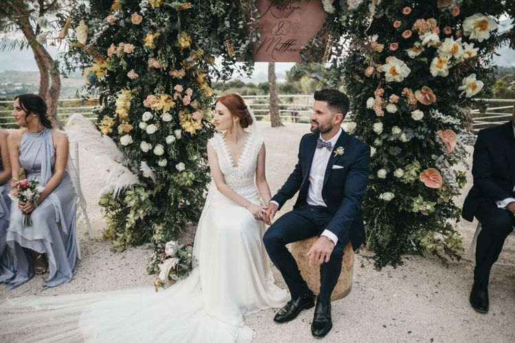 Bride and Groom Holding Hands During the Wedding Ceremony with a Floral Arch Backdrop
