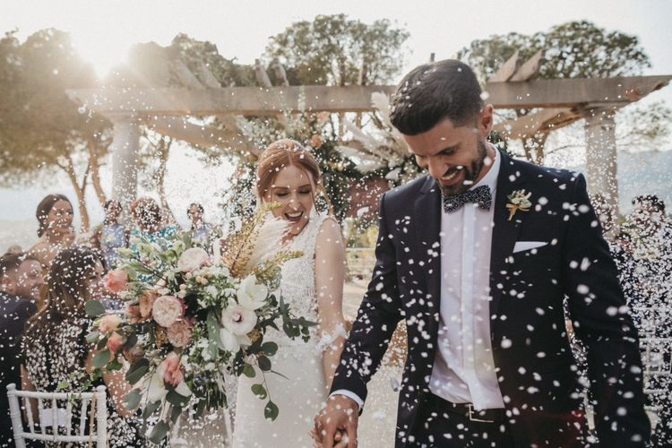Confetti Moment with Groom in Tuxedo and Bride in Pronovias Wedding Dress