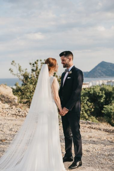 Bride and Groom Holding Hands on a Spanish Cliffside