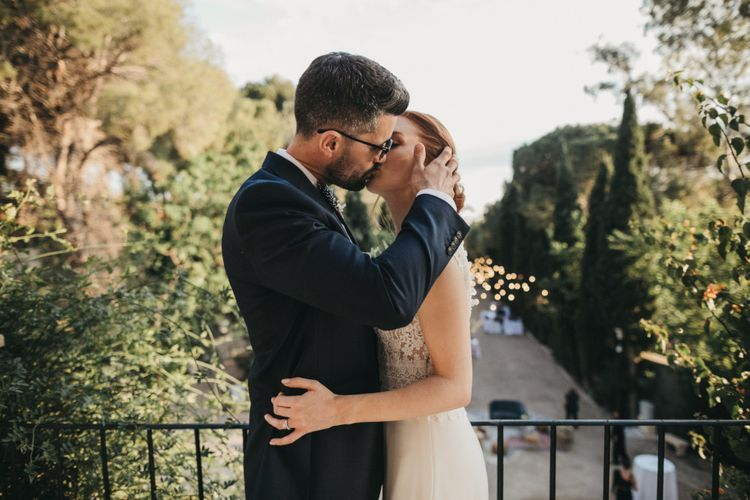 Groom in Navy Suit Kissing His Bride on the Balcony
