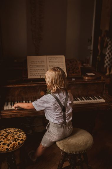 Young Boy in Shorts and Blazer Sitting at a Piano
