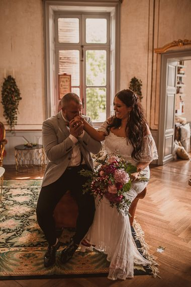 Groom in Grey Blazer and Bow Tie Kissing His Brides Hand in an Off The Shoulder Wedding Dress