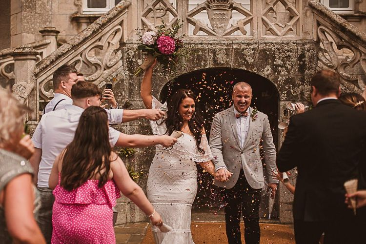 Confetti Moment with Bride in Grace Loves Lace Wedding Dress and Groom in Grey Blazer and Bow Time