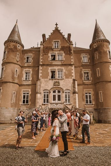 Bride in Grace Loves Lace Wedding Dress and Groom in Grey Blazer and Bow Time Kissing in Front of the French Chateau featured on escape to the chateau