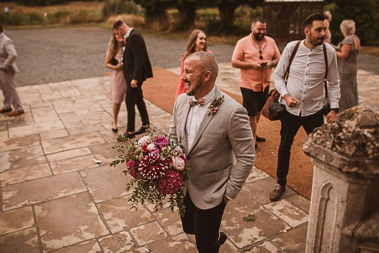Groom in Grey Blazer and Bow Tie Holding a Pink Wedding Bouquet featured on escape to the chateau