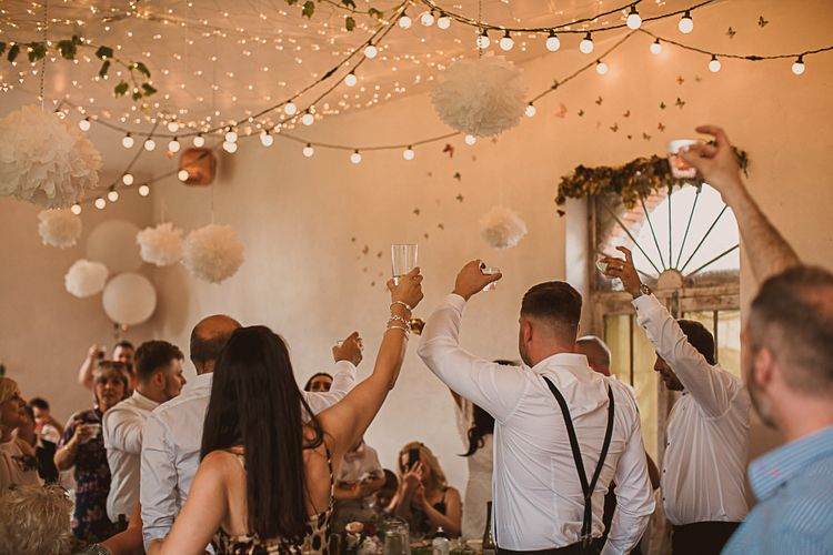 Wedding Guests Raising a Glass in the Festoon Lit Wedding Reception