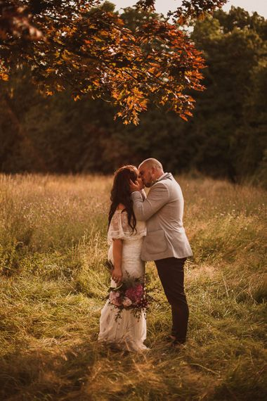 Bride in Emanuela Grace Loves Lace Wedding Dress and Groom in Grey Blazer Kissing in a Field