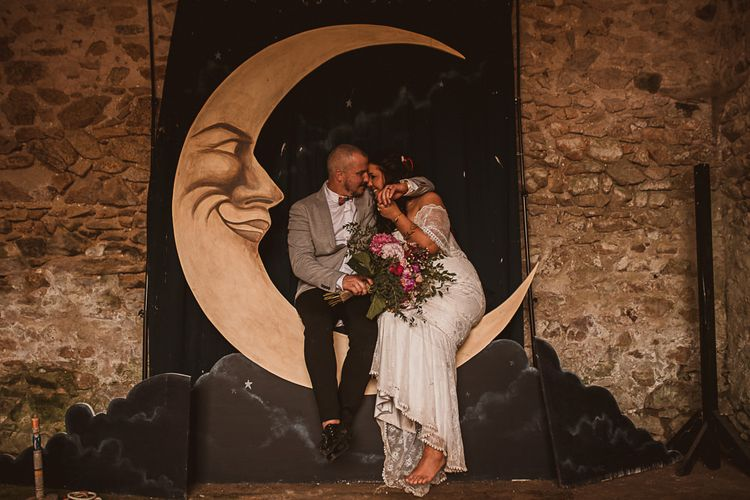 Bride in Emanuela Grace Loves Lace Wedding Dress and Groom in Grey Blazer Embracing on a Giant Moon