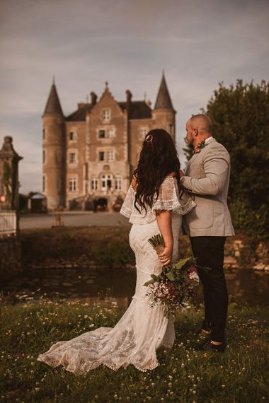 Bride in Emanuela Grace Loves Lace Wedding Dress and Groom in Grey Blazer Standing in Front of Their French Chateau Wedding Venue