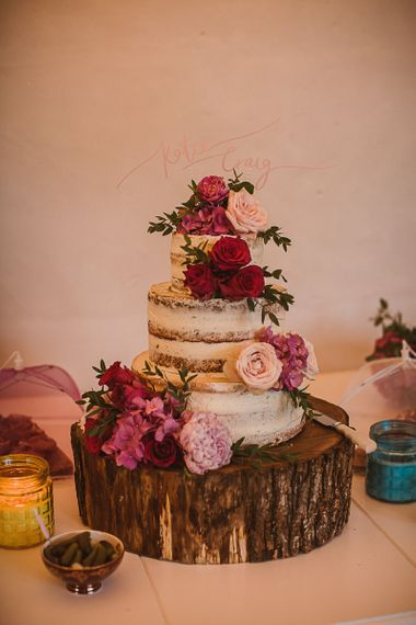 Semi Naked Wedding Cake Decorated with Pink Flowers on a Rustic Tree Slice Cake Stand escape to the chateau