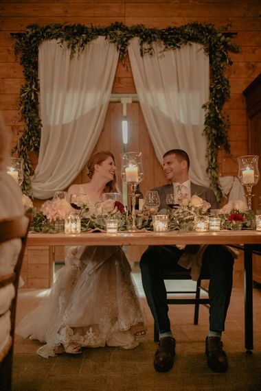 Sweetheart Table with Candle Light and Drapes Backdrop