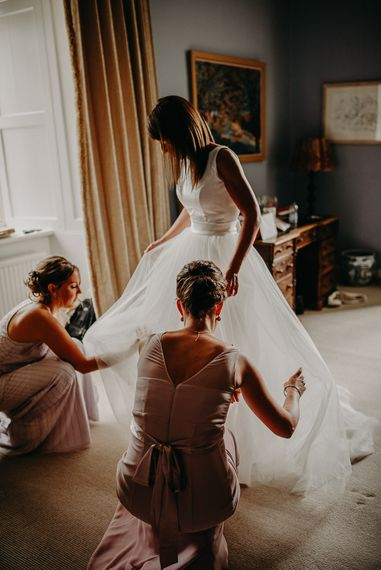 Bride getting ready in satin and tulle wedding dress