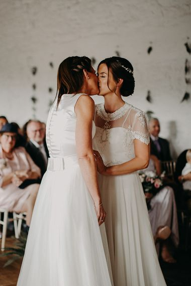 Same sex wedding with two brides kissing at the altar