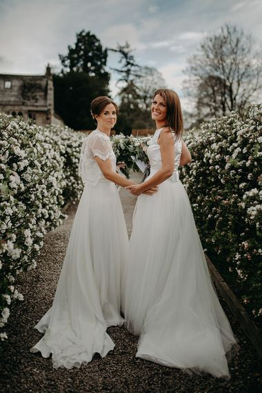 Lesbian wedding with two brides in chiffon and lace and satin and tulle bridal gowns