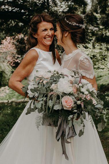 Lesbian wedding portrait with brides holding romantic bridal bouquets