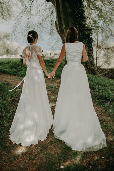 Same sex wedding with two brides in Satin and tulle dress and Lace and chiffon wedding dress holding hands