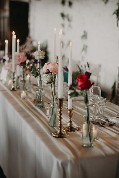 Top table  decor with taper candles and flower stems in vases