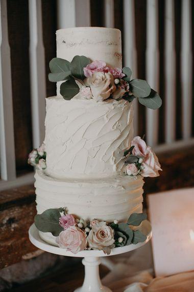 Three tier buttercream cake with roses and eucalyptus decor