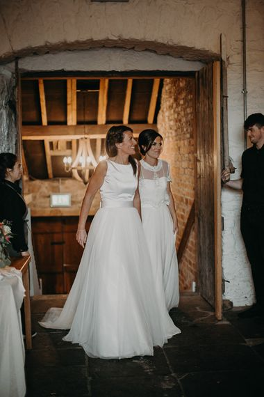 Two brides entering the reception at Askham Hall