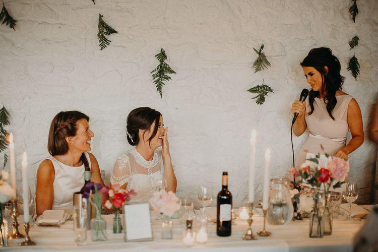 Bridesmaid in pink dress delivering wedding speech