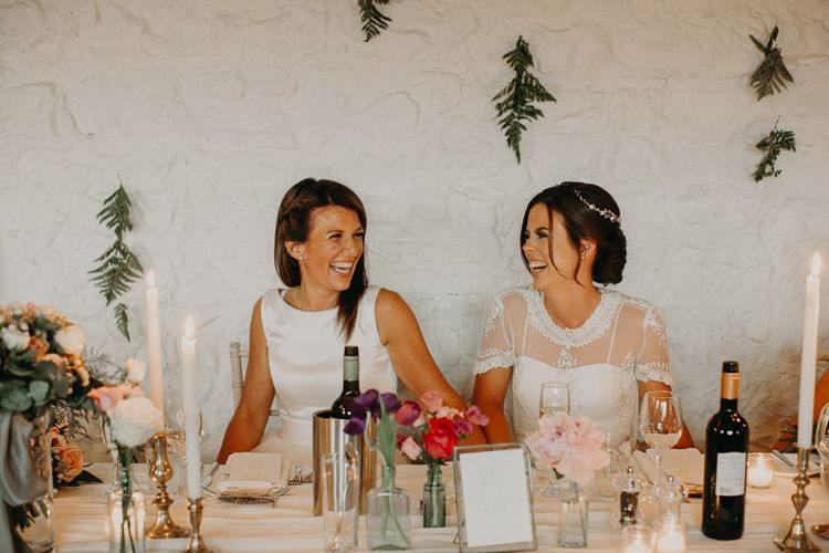 Two brides laughing at their same sex wedding reception