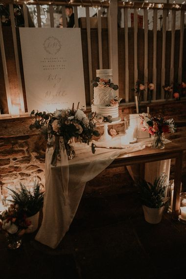 Wedding cake table with romantic candlelight, drapes and flowers decor
