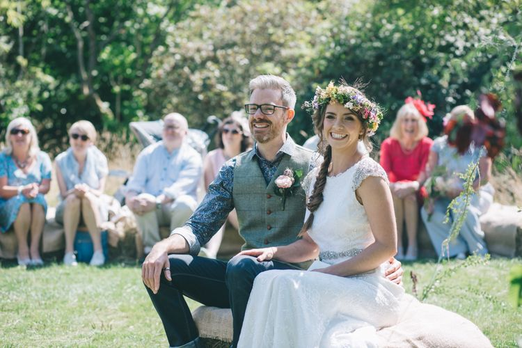 Bride in Lusan Mandongus Wedding Dress and Flower Crown and Groom in Floral Shirt and Tweed Waistcoat During the Wedding Ceremony
