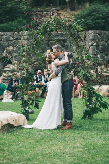 Bride  in Lusan Mandongus Wedding Dress and Flower Crown and Groom in Floral Shirt and Tweed Waistcoat Kissing at the Altar