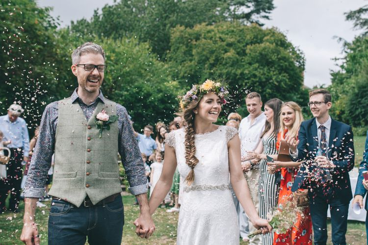 Confetti Moment with Bride  in Lusan Mandongus Wedding Dress and Flower Crown and Groom in Floral Shirt and Tweed Waistcoat