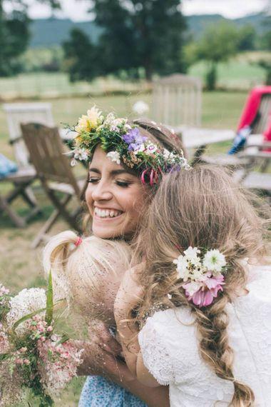 Bride with Wildflower Crown Embracing Her Flower Girls