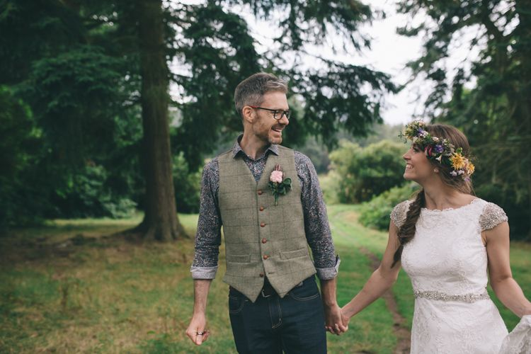 Bride in Lusan Mandongus Wedding Dress and Flower Crown and Groom in Floral Shirt and Tweed Waistcoat  Holding Hands