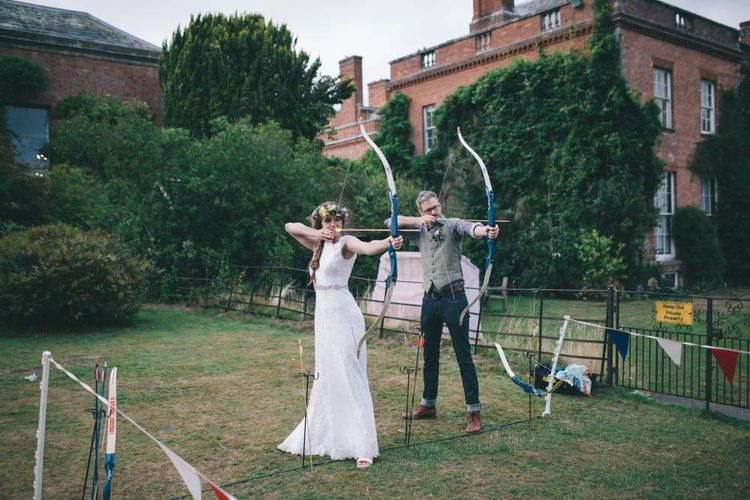 Bride in Lusan Mandongus Wedding Dress and Flower Crown and Groom in Floral Shirt and Tweed Waistcoat   Shooting Archery