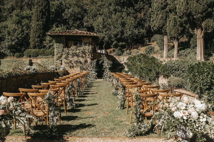 Outdoor wedding ceremony with foliage chair decor