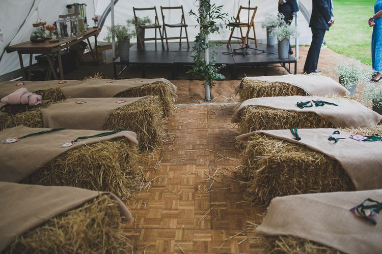 Haybale Seating For Wedding Ceremony // Rainy Festival Wedding In East Sussex With Bride In Rime Arodaky And Black Biker Boots And Bridesmaids In White Dresses With Silent Disco Party Images By Jesus Caballero